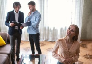 Young lady looking at new house while her husband and real estate agent discussing ownership